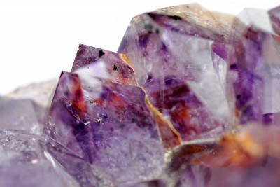 11061675-close-up-view-to-raw-amethyst-crystals-on-white-background-studio-shot-not-isolated